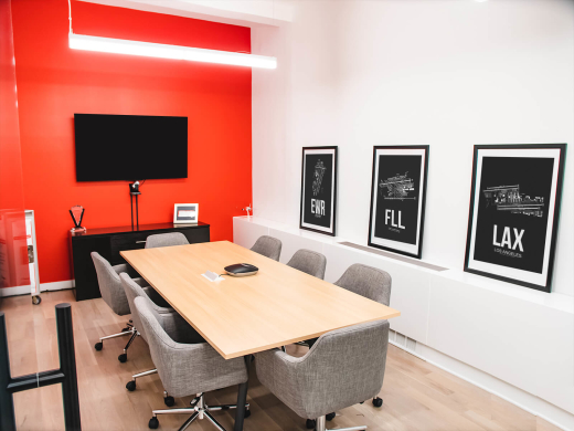 Norwegian Air office interior design by Basicspace. Display of conference room with vibrant Norwegian red accent wall with airport artwork displayed.