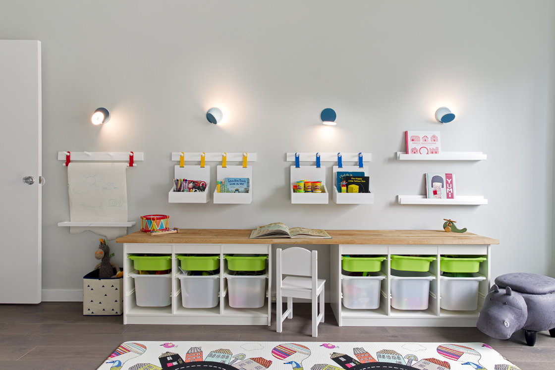 Lincoln Tower Apartment residential interior design renovation by Basicspace. Playful kids desk and wall storage with adjustable lighting. Art bins, baskets, shelving, and wall hooks for easy access to toys, arts and crafts, and books.