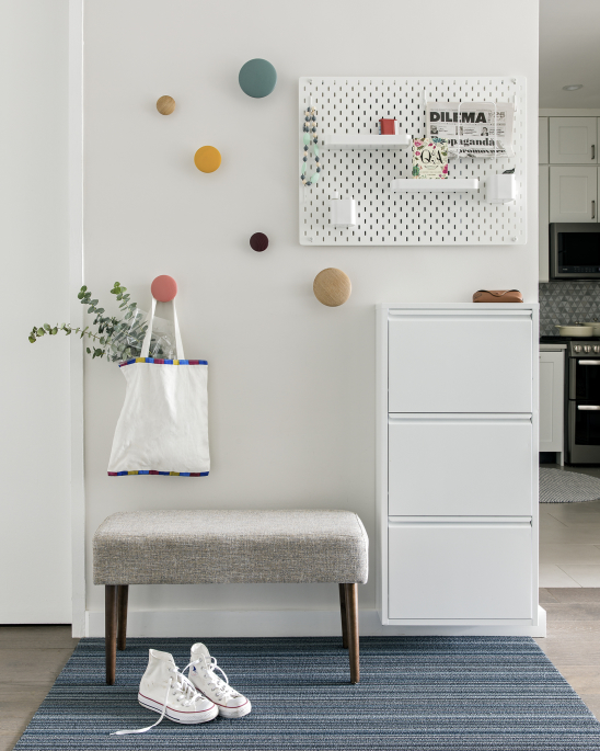 Lincoln Tower Apartment residential interior design renovation by Basicspace. Playful and welcoming entry foyer with polka dot coat hooks and wall mounted shoe storage and accessories organizer with small bench below.