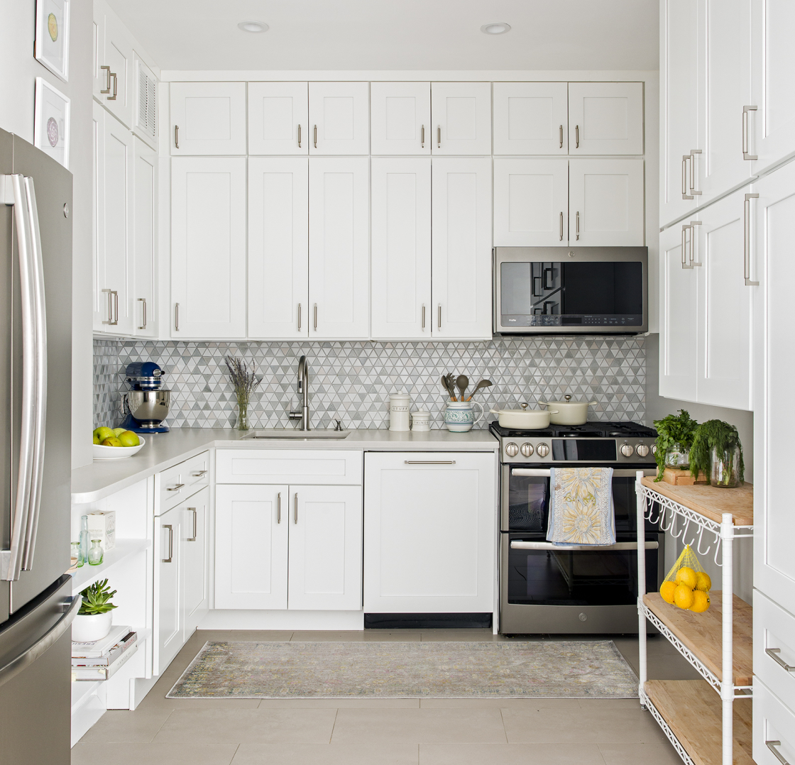 Lincoln Tower Apartment residential interior design renovation by Basicspace. White kitchen cabinetry with mosaic backsplash, light grey counters and matte slate appliances and butcher block cart.