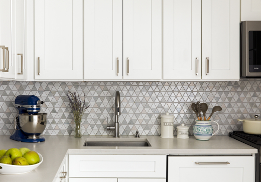 Lincoln Tower Apartment residential interior design renovation by Basicspace. Balanced triangular mosaic backsplash accenting white cabinets and light grey counters.