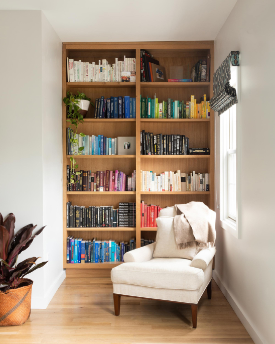Jersey City Condo residential interior design by Basicspace. Color coded open bookcase shelving in reading nook.