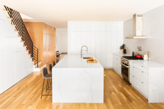 Jersey City Condo residential interior design by Basicspace. White kitchen, open stair, wood flooring with wood wall paneling. Pot filler with hood above range, stainless steel sink, pull down faucet and quartz waterfall countertop island.