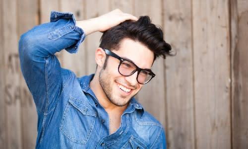 Mann mit vollem Haar lächelt nach einer Saphir Haartransplantation.