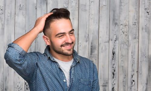 Uomo che sorride dopo un trattamento di trapianto di capelli