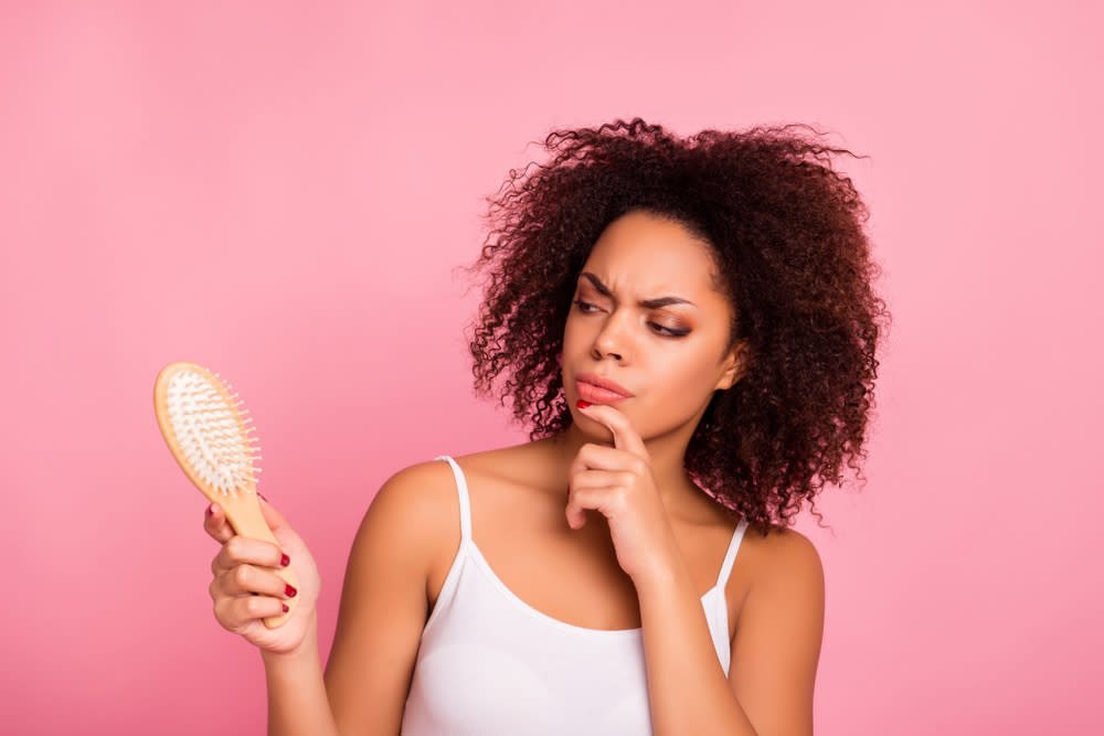 Una mujer mira un cepillo mientras considera hacerse un trasplante de pelo.
