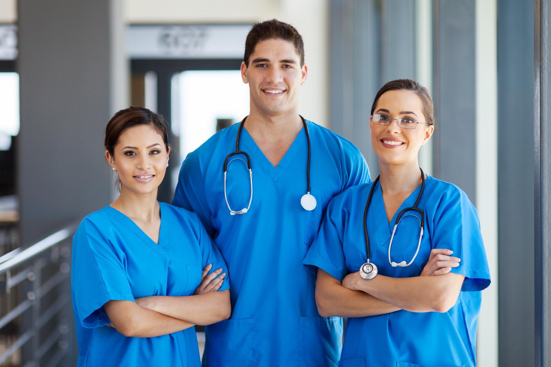 Técnicos de trasplantes capilares femeninos y masculinos con bata en un hospital