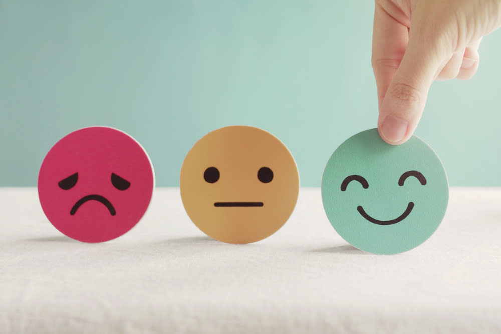 Picture of a person picking a happy face out of neutral and sad face