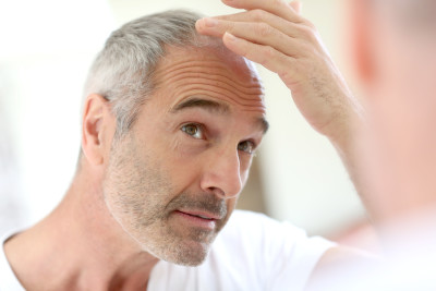 Older balding man looking in the mirror at his hairline