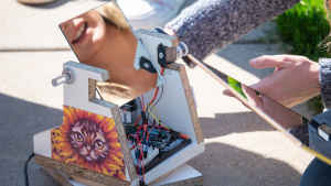 A female student's smile is reflected in the mirror of a solar powered camera built from wires and particle board by her and her classmates. On the machine is taped a printout of a cat wearing a sunflower costume.