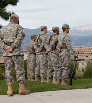Four US Army soldiers and their commander stand at attention to the US flag on the University of Colorado Colorado Springs campus.