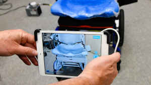 A pair of hands holds a smart tablet to take a digital screening for measurements of foam padding on the seat of a motorized wheelchair