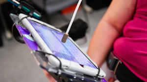 A woman wears an long skinny instrument with a soft tip to push the keyboard buttons on her smart tablet to compose an email.