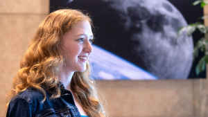 Willow Reed looks to the side as her long red wavy hair falls in front of her jean jacket. On the wall behind her is a large black and white artwork of the moon.