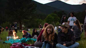 College students sit on blankets on the ground as dusk settles in along the flatirons. They are on a field trip, taking notes by lantern and lamp about the night sky.