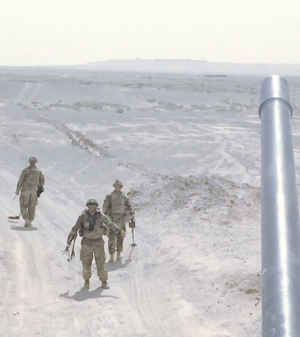 Three US Army soldiers walk along a barren desert road in Afghanistan scanning the ground for IEDs