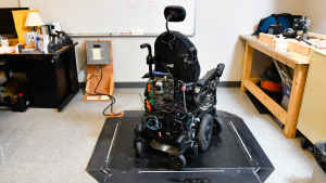 Designed by a student, a test wheelchair sits idle on a solar charging pad.