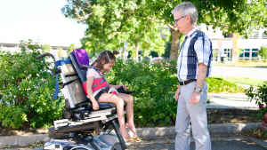 In a parking lot outside the clinic, a young girl gleefully laughs as she moves the motorized wheelchair forward for the first time. A male occupational therapist looks on.