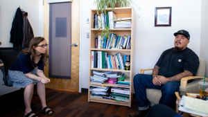 A female mental health clinican leans over in her chair to listen to a veteran sitting across from her during a therapy session. A bookcase filled with books and plants is against the wall.