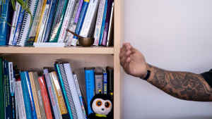 A heavily tattooed arm of a man is extended as the veteran tells how he survived combat in front of a bookcase filled with self-help books, a stuffed animal and other trinkets.