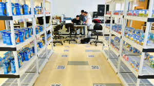 Three male CU students cluster around a laptop at the front of a classroom, where a mock warehouse has been set up with shelves lined with cans and boxes of food. QR codes line the floor.