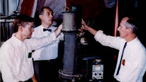 An old historic photo where three male scientists, one with a pocket protector, one with a bowtie and one with a skinny tie, stand around holding an early rocket.