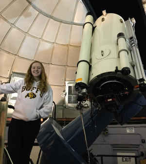 Willow Reed as an undergraduate student at CU stands in front of a large telescope. She is smiling and wearing a white CU Boulder sweatshirt.