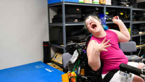 A woman with bright blue hair and wearing glasses throws her head back to laugh as she sits in her wheelchair in the clinic.