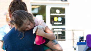 A mother carries her barefoot daughter across a parking lot. The young girl rests her head on her mother's shoulder and clutches her stuffed animal - a faded pink bunny wearing a bright pink cape - as they enter the clinic.