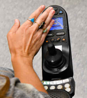 A female's hand wearing rings on three fingers, touches the cracked screen on the joystick of her motorized wheelchair.