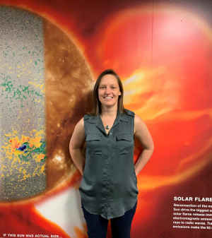 A female scientist stands with her hands on her hips in front of a wall showing red and yellow images about solar flares.