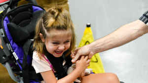 A young girl laughs after she kisses the hand of her occupational therapist.