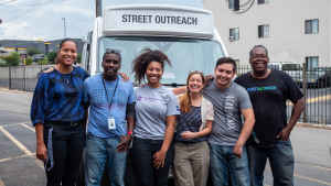 A group of CU students and researchers smile and stand in front of a van with community organizers before they begin their street outreach in Aurora, Colorado.