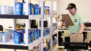A young man walks holds a clipboard and looks at a shopping list while pushing a cart in a mock warehouse. The shelves are lined with cans and boxes of food.