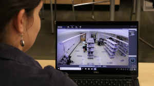 A female CU student watches on a computer screen live video of a client walking through the mock warehouse to monitor his movements.