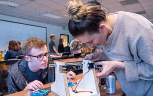 A male college student kneels to get a better look at a solar-powered camera his female classmate is leaning over. She is trying to attach wires and other materials to make it function. They are inside a classroom where other students are also trying to build similar projects.