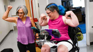 A clinic coordinator and woman in a wheelchair both flex their forearms triumphantly and smile.