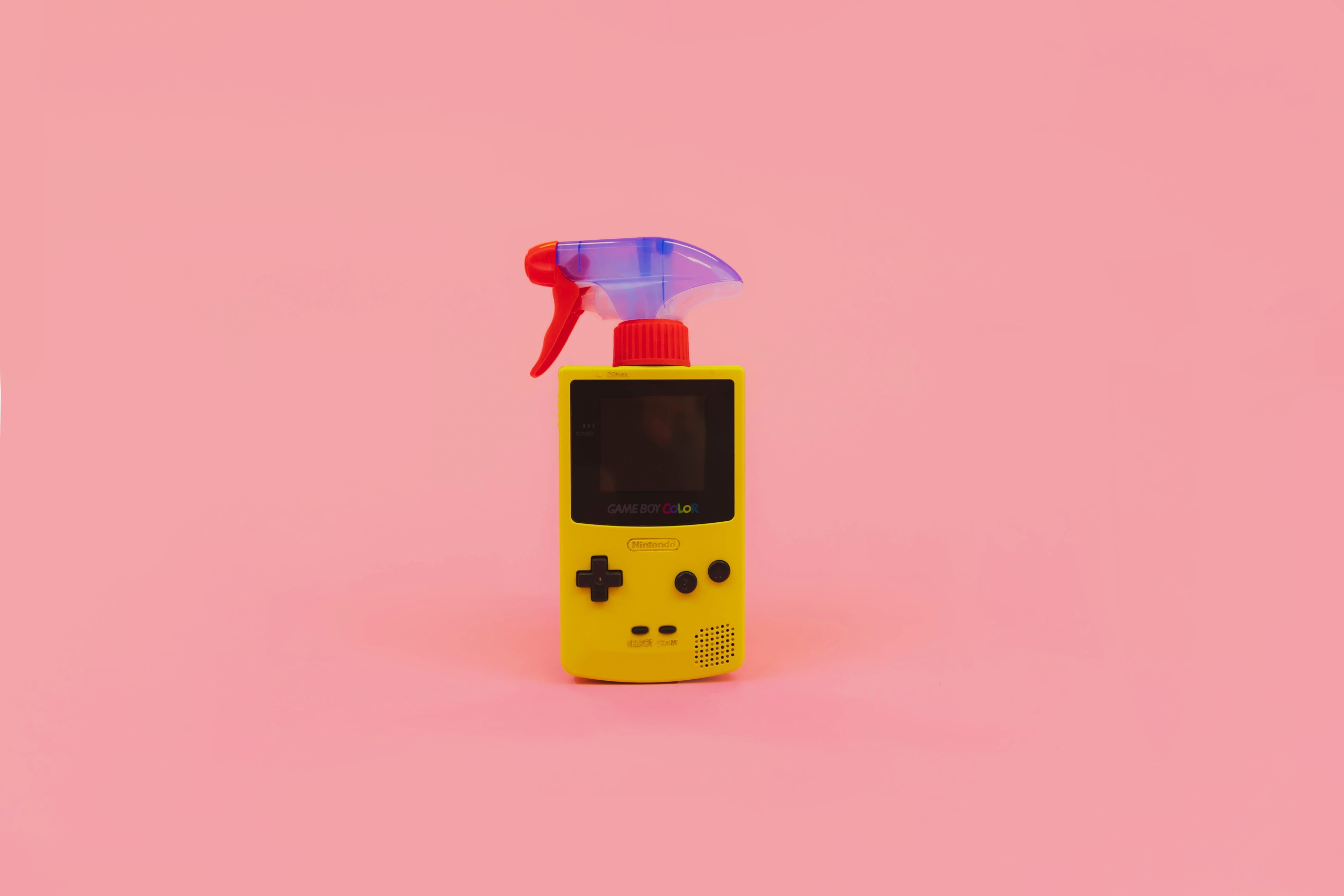 game-boy-yellow-pink-background-cleaning-spray-on-top