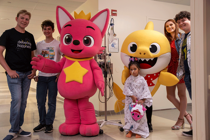 Kids in pediatric playroom posing with Baby Shark and Pinkfong