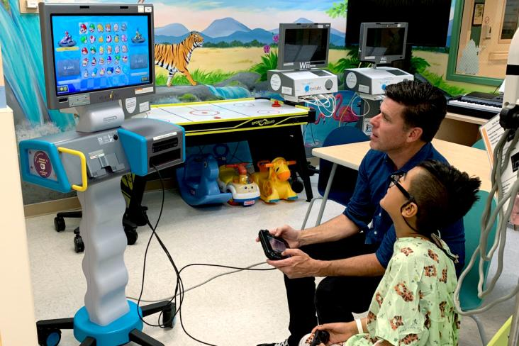 Adam Garone at a hospital sitting with a child in the hospital playing on a Nintendo Switch gaming station