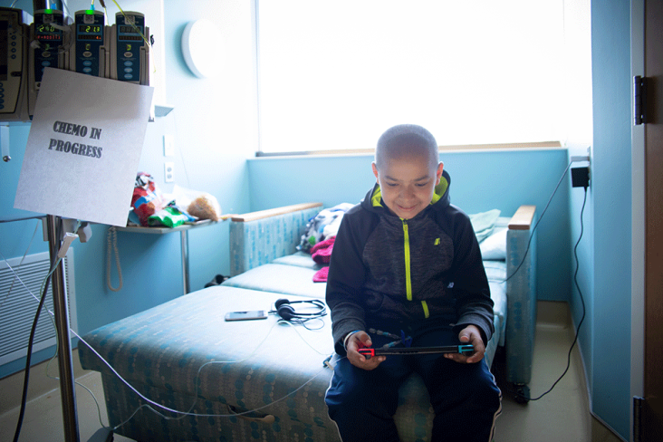 Boy playing with Starlight gaming undergoing chemo in hospital