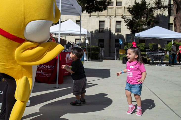 Little girl at LAC+USC Kidz Health Fair playing with giant stuffed animal