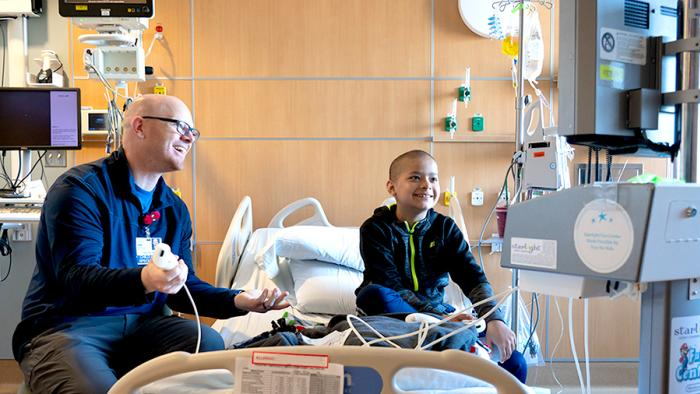Boy playing Gaming console in hospital