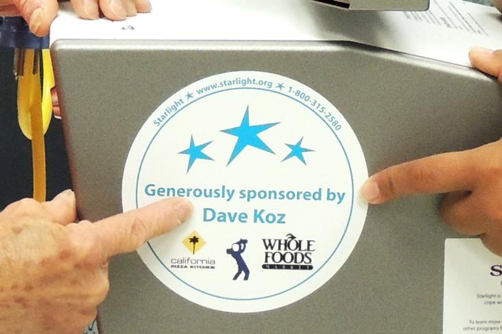 "A Wii gaming station with a sticker ""Generously sponsored by Dave Koz"""