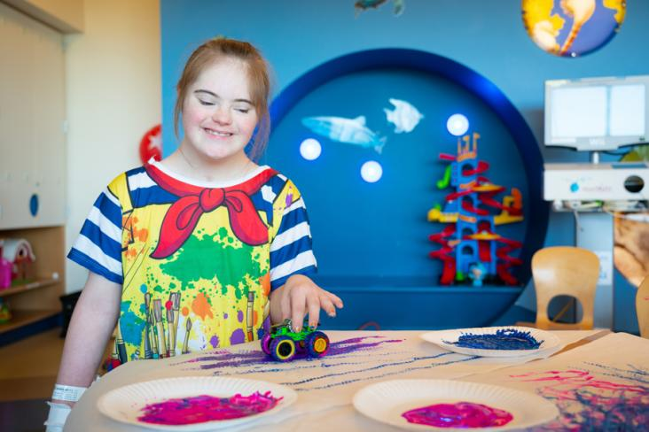 A girl in the hospital with a starlight hospital gown on playing with toys and paint