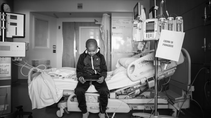 "Kid alone in the hospital playing by himself with a ""Chemo In Process"" sign next to him"