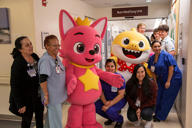 Pinkfong and Baby Shark posing with some of the patients in the pediatric unit