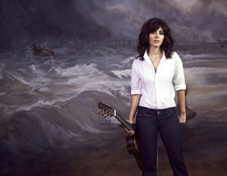 Katie Melua portrait in front of painting of a beach