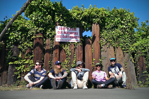 The Dirty Heads band sitting outside in front of wood fence