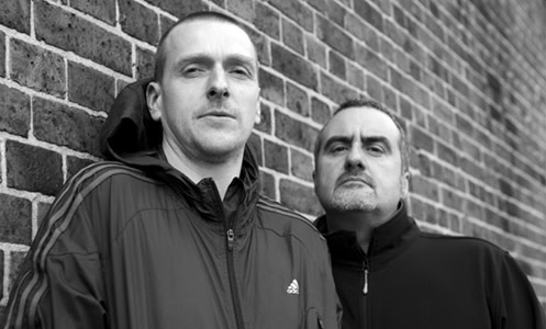 Godflesh black and white photo in front of brick wall